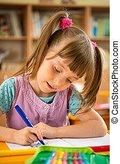 Little schoolgirl sitting behind school desk during lesson in school
