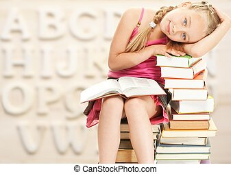 Little schoolgirl sitting on books
