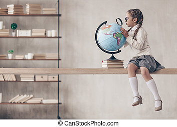 Little schoolgirl with a globe