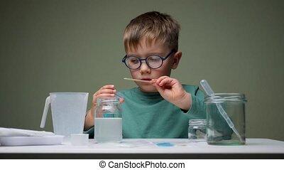 Little scientist doing experiments. Education concept. Child doing chemical research in laboratory. Dangerous experiment. Home activities for children. Preschooler interests