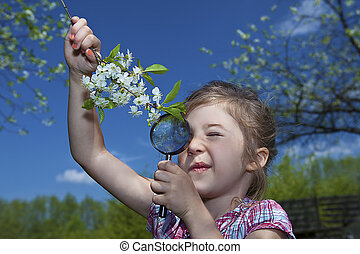 little girl with magnifying glass checking flowers