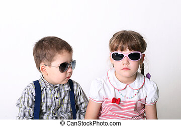Little serious boy and girl sit in sunglasses in white studio