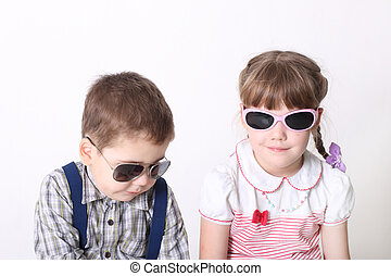 Little serious boy and smiling girl sit in sunglasses in white studio