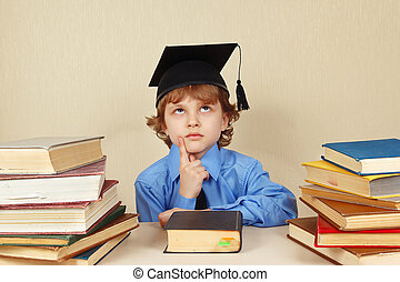Little serious boy in academic hat among old books - Little...
