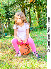Little seven year old girl sitting on the ball