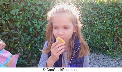 little shaggy girl eating a bun on the street in the Park. walks and light snacks in nature.