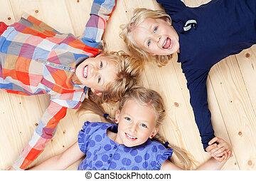 Little Siblings Lying On Hardwood Floor - High angle view of...