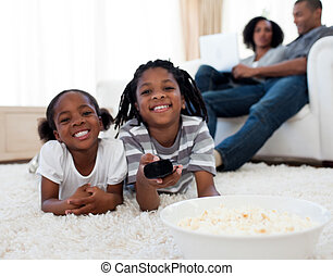 Little siblings watching television and eating pop corn in...