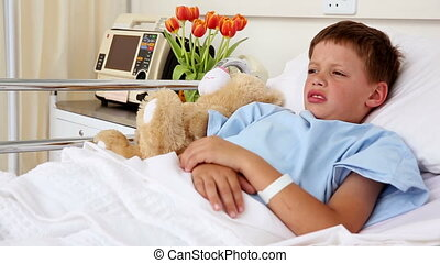 Little sick boy lying in bed with stuffed bear