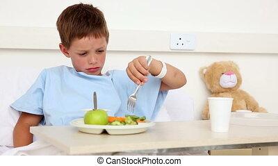 Little sick boy sitting in bed having lunch