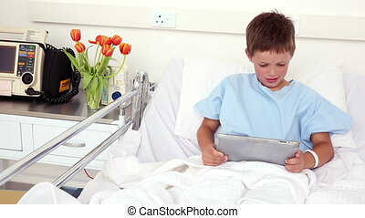 Little sick boy sitting in bed using tablet PC