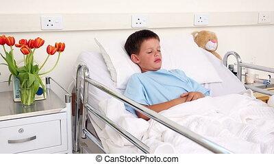 Little sick boy sleeping in bed