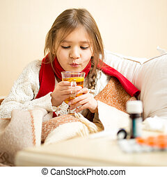 little sick girl lying in bed and blowing on hot tea