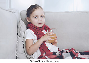 Little sick girl sits on a white couch wrapped in a red scarf. She is sitting with a cup of medicinal tea