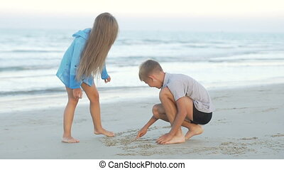Little sister and brother draw on sand.