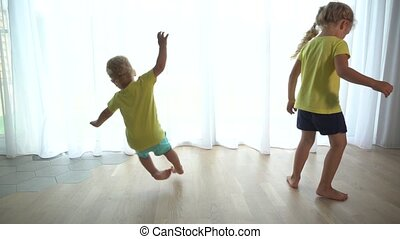 Little Sister girl and Young Adorable Brother Spin around at Home