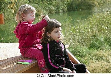 Little sister girls hairdresser on the river