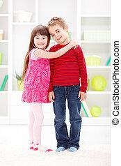 Little sister hugging her brother