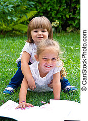 little sisters are resting on the green grass in summer with book