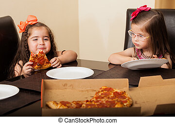 Little sisters eating pizza at home