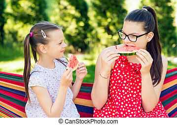 Little sisters friends eating watermelon slices in the garden sitting on a hammock