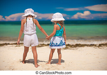 Back view of two little sisters looking at the sea on the white beach