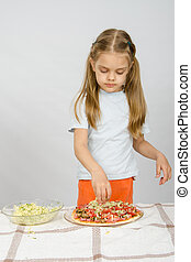 Little six year old girl standing at the table and sprinkle with grated cheese pizza