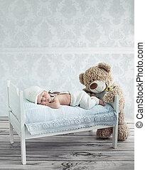 Little sleeping baby and the teddy bear