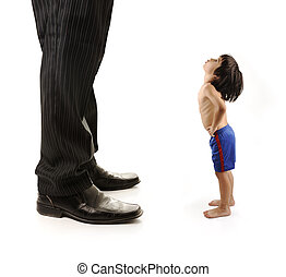 Little small child is looking at the giant legs of ...