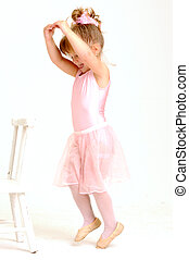 Little smiley girl wearing a pink ballet outfit is dancing...