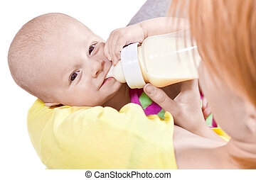 Little smiling baby and bottle on the ands of his mother