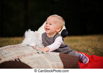 Little smiling baby girl sitting on a blanket in the park