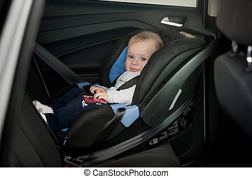 Little smiling baby on back seat