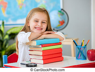 Little smiling blond girl holding hands on the books in the school classroom