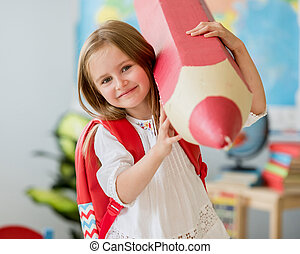 Little smiling blond girl holding huge red pencil in the school classroom