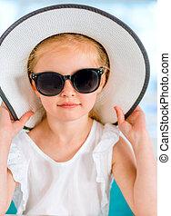 Little smiling blond girl in black sunglasses