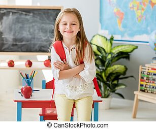 Little smiling blond girl standing in the school class