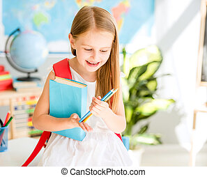 Little smiling blond girl standing in the school classroom