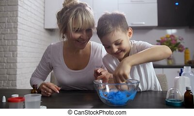 Little smiling boy actively mixing mass for slime - Cute...
