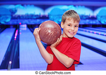 Little smiling boy dressed in red T-shirt holds ball in...