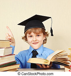 Little smiling boy in academic hat quoted old book - Little...