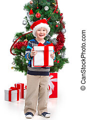 Little smiling boy in Santa hat holding present. Standing over white background with Christmas tree