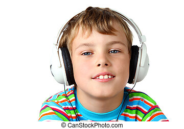 Little smiling boy in striped shirt and headphone listening...