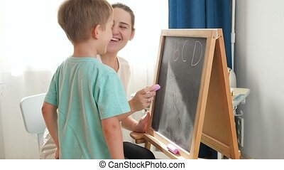 Little smiling boy learning ABC with young mother at home. Teacher writing alphabet on blackboard with chalk. Home education and remote school.
