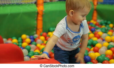 Little smiling boy playing in colorful balls