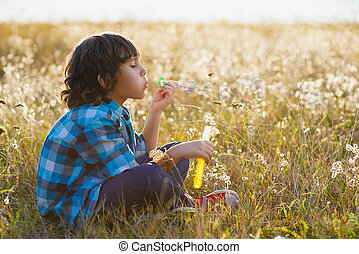 Little smiling boy playing soap bubbles in summer park outdoor