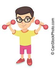 Little smiling caucasian boy holding dumbbells.