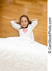 smiling girl covered with blanket lying on wooden floor