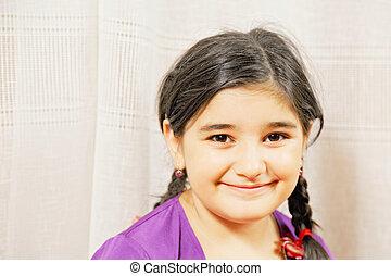 Little smiling girl in purple dress