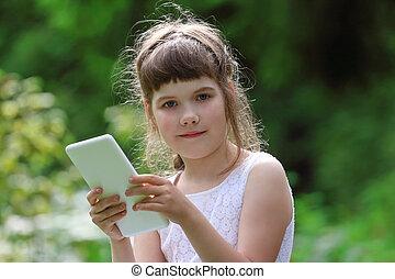 Little smiling girl in white dress holds white tablet pc in park at summer day